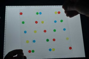 Charge-selective (yellow and green) and freshwater and saline (blue and red) hydrogels, printed on a sheet that has been laser-cut in a Miura fold pattern. IMAGE: Biophysics group, Adolple Merkle Institute