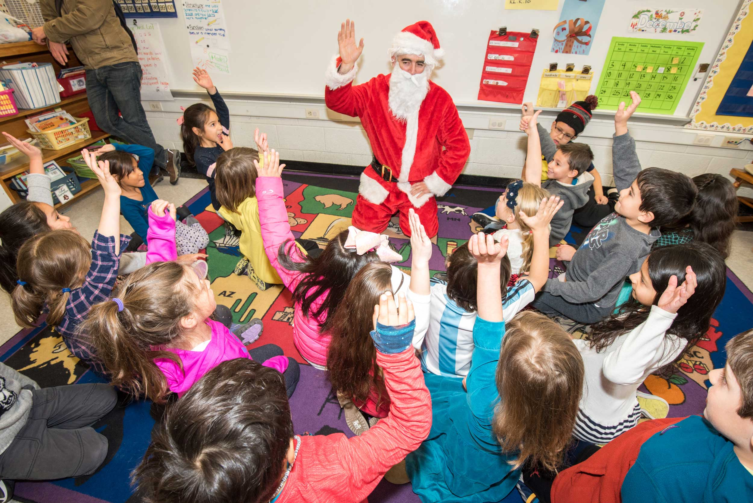Santa pays a visit to second graders at the Spanish Language Program En Nuestra Lengua before the end of the semester.