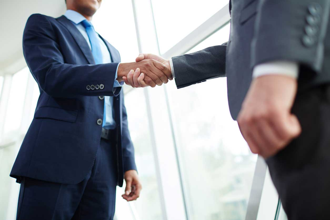Two people in suits shaking hands. (stock image)