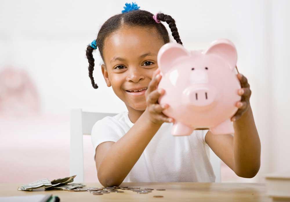 Menina mostra seu cofrinho e gosta de economizar. (imagem de estoque)