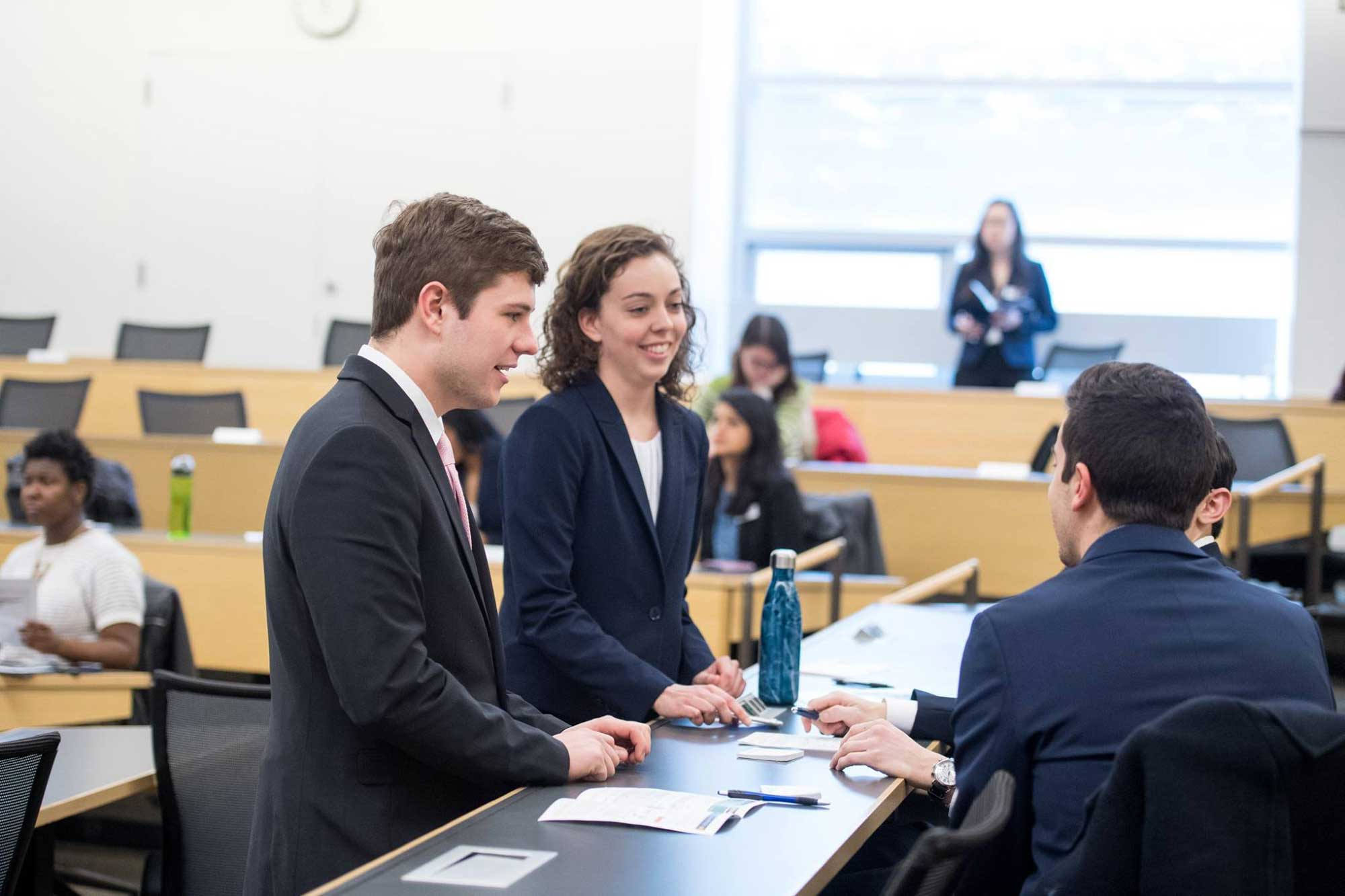 Nick Walsh, left, and Brie Riley, both juniors at the University of Michigan Ross School of Business, confer with other members of team Upstart during the Social Impact Challenge competition finals on Feb. 6, 2018. The team won $3,000 for their ideas to spur pop-up businesses in Detroit neighborhoods. Image credit: Michigan Photography