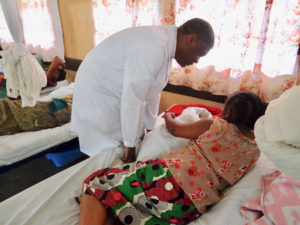 Dr. Denis Mukwege conducting rounds in the fistula ward and visiting a patient her bedside.