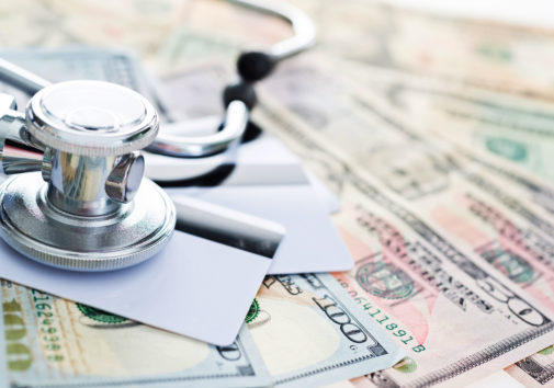 Stethoscope on credit cards and us paper currency, healthcare costs concept.