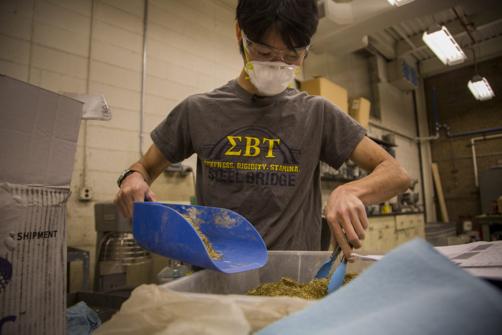 Isaya Miyata, undergraduate in civil and environmental engineering, prepares Ultra High Performance Concrete. UHPC is a new class of concrete that utilizes a low water content as well as steel fibers mixed in for extra density. Once set, the concrete is able to take on 6-7 more impact load than regular concrete before it fails. While UHPC is more expensive than regular concrete, the cost savings using this stronger, longer-lasting concrete could be significant. Image credit: Robert Coelius, Michigan Engineering