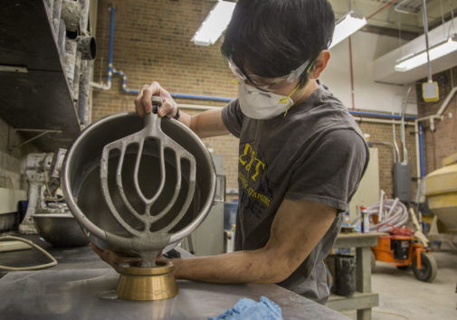 Isaya Miyata pours the concrete formula into a mold. Image credit: Robert Coelius, Michigan Engineering