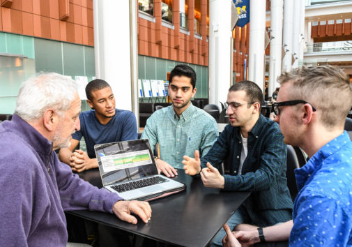 Students Tristan Neeb, Aklavya Kashyap, Shayan Shafii and Sean Dew talk about next steps with their instructor, Robert Pasick of the Ross School, on the goal tracking voice assistant they created for use with Amazon's Alexa. Image credit: Randy Maschaka