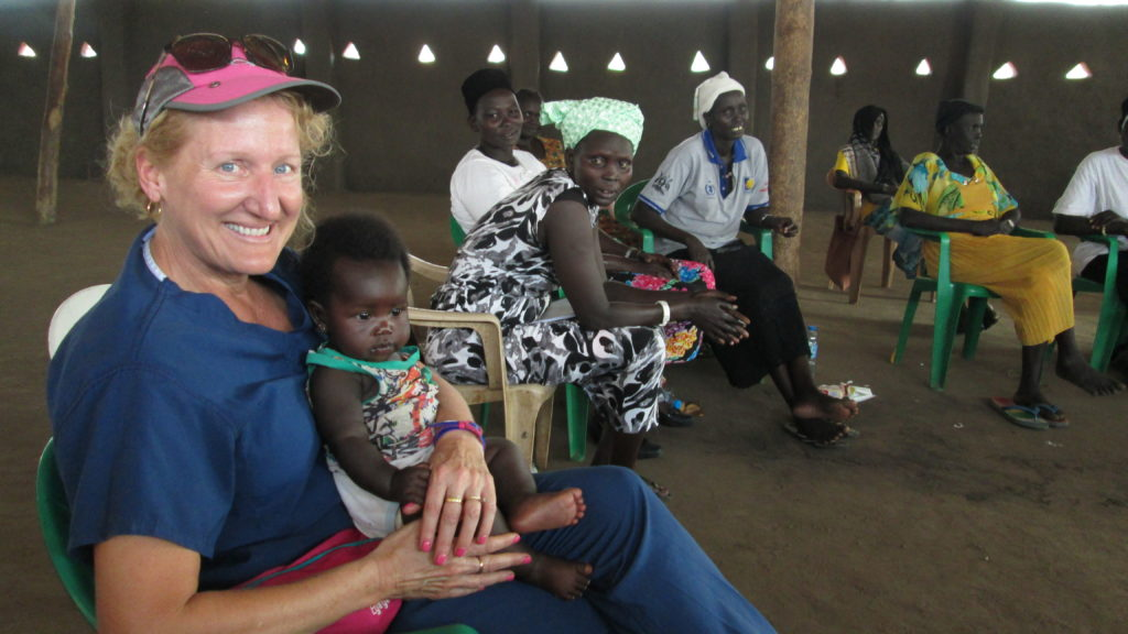 Ruth Zielinski, associate professor in the U-M Nursing School, holds a baby whose mother is taking Zielinski's class on family and child health in a Ugandan refugee camp.