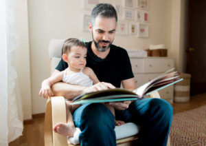 A mid adult father sitting on a chair with baby on lap at home and reading a book in a horizontal medium shot indoors.