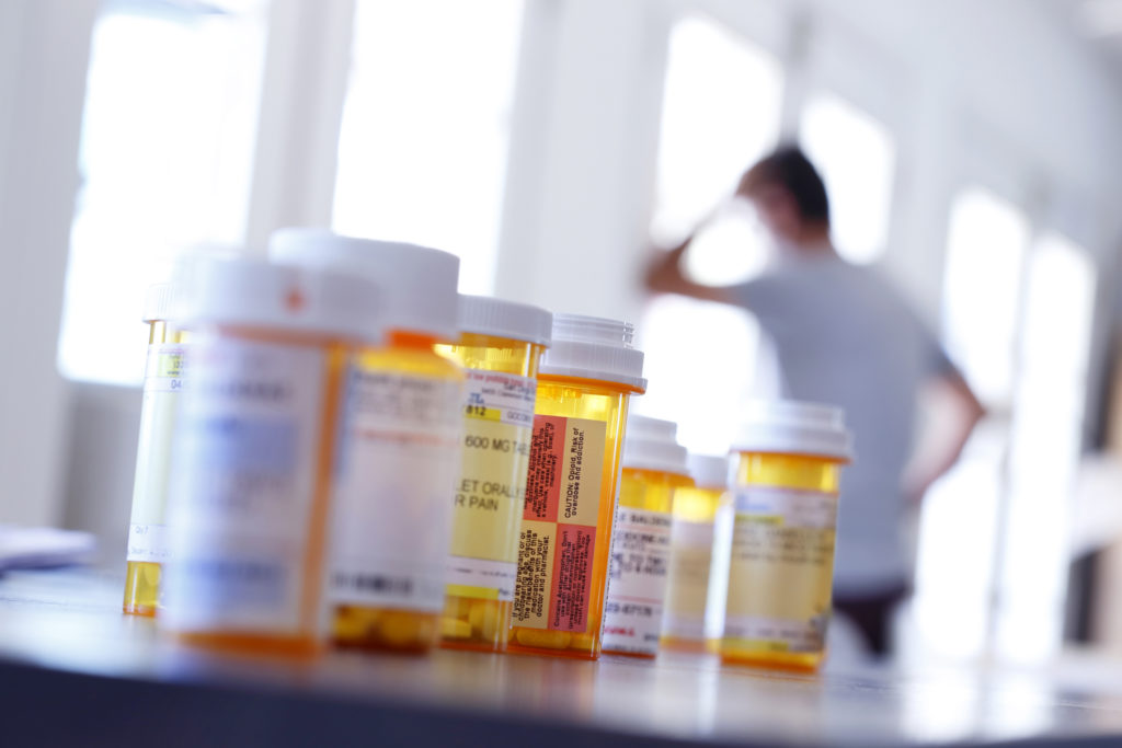 A large group of prescription medication bottles sit on a table as a man in the background leans against a wall with his hand on his head.. The image is photographed with a very shallow depth of field with the focus being on the pill bottles in the foreground.