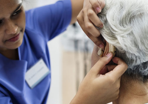 doctor putting hearing aid into older woman's ear