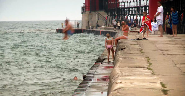 people swimming and jumping off pier into lake michigan