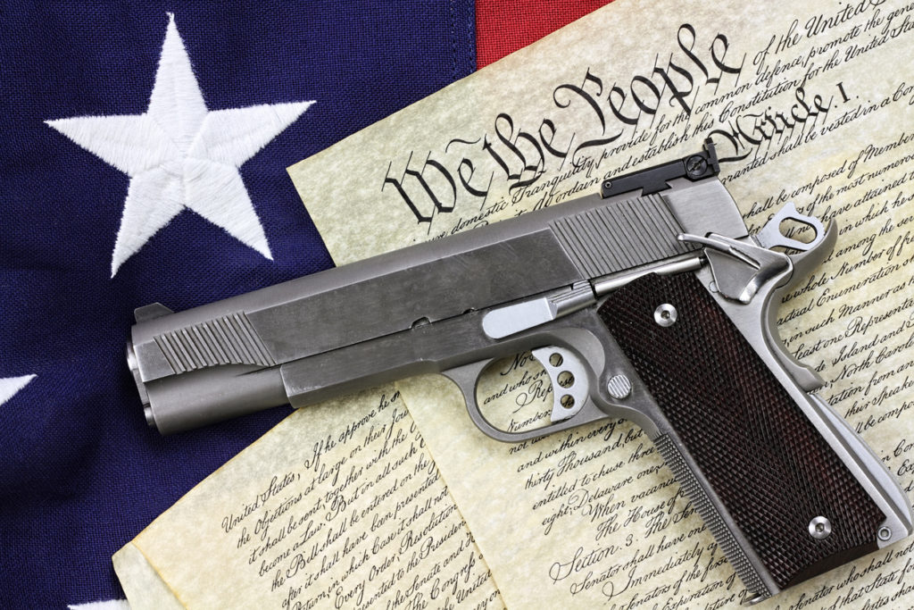 Handgun lying over a copy of the United States constitution and the American flag. (iStock image)