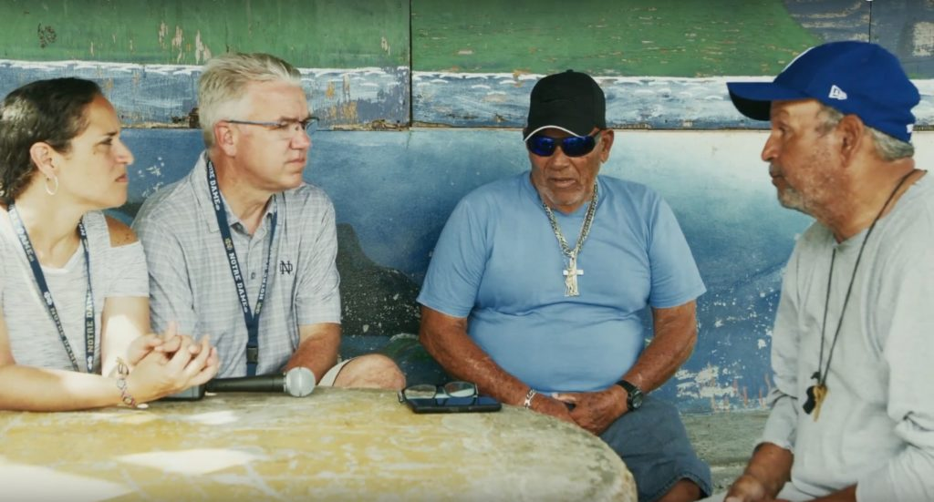University of Notre Dame faculty, Marisel Moreno and Thomas Anderson, speak with two Puerto Rican men about their experiences with Hurricane Maria.