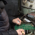 A e-waste recycler solders a printed circuit board in Chile.