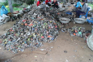 Pile of waste in Thailand with five workers separating metal and plastic components for resale or recycling.