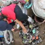 An e-waste recycler works to take a motor apart in Thailand.
