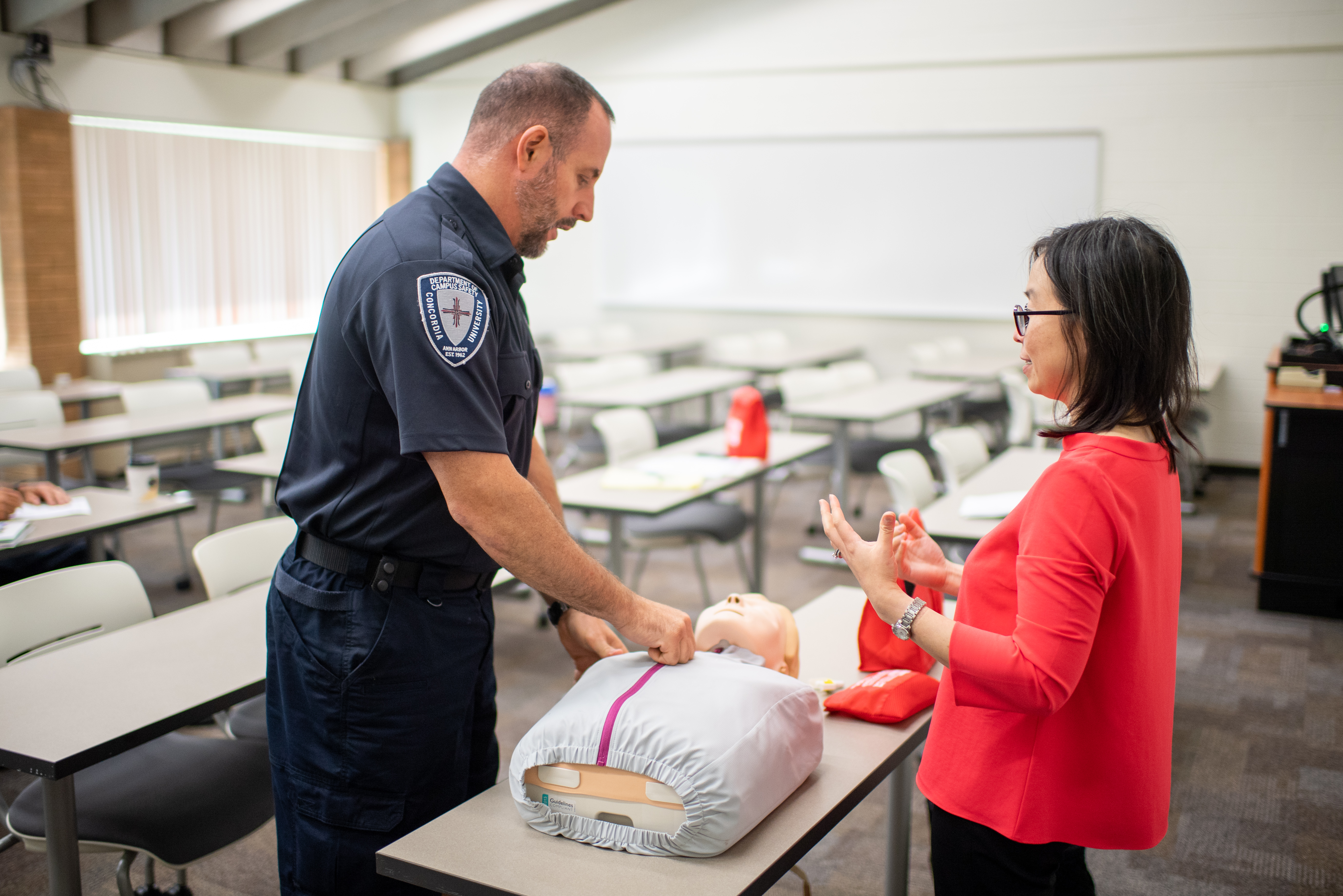Chin Hwa (Gina) Dahlem discusses overdose treatment with Christopher Imperati, assistant campus safety director at Concordia University. Image credit: Chris McElroy, Michigan Photography