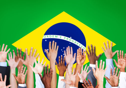 Group of Multi-Ethnic Arms Raised and a Flag of Brazil as a Background