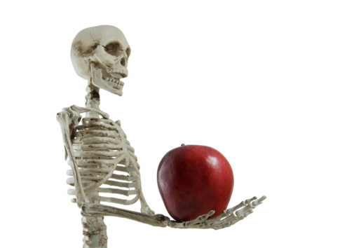 Skeleton holding an apple isolated on white. (iStock image)