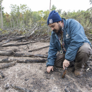 U-M doctoral student Buck Castillo uses the burn plots to study how forest disturbances affect fungal communities in the soil. Here, he inspects the burn plot the morning after the Oct. 10 prescribed fire.