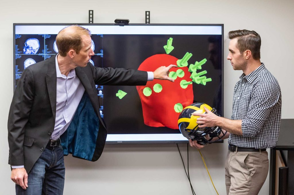 Steven Broglio (left) of the School of Kinesiology and kinesiology student Griffin Feinberg discuss football impact biomechanics and how they relate to brain function. Each arrow indicates a head impact. Image credit: Scott Soderberg, Michigan Photography