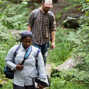 "U-M wildlife ecologist Nyeema Harris and graduate student Corbin Kuntze heading into the forest at the University of Michigan Biological Station to install ""camera traps"" to capture wildlife images. The Biological Station is one of three Michigan sites in the study, which will yield hundreds of thousands of wildlife snapshots."