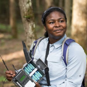 U-M wildlife ecologist Nyeema Harris holding one of the camera boxes, which contain batteries.