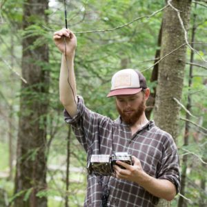 U-M graduate student Corbin Kuntze checks the strength of the cellular signal at a Biological Station camera site. A few of the cameras are equipped with transmitters that send photos directly to the researchers' email inboxes in real time.