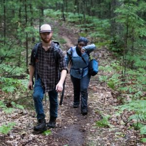 Kuntze and Harris head out of the forest after installing three cameras on a rainy July morning at the U-M Biological Station.