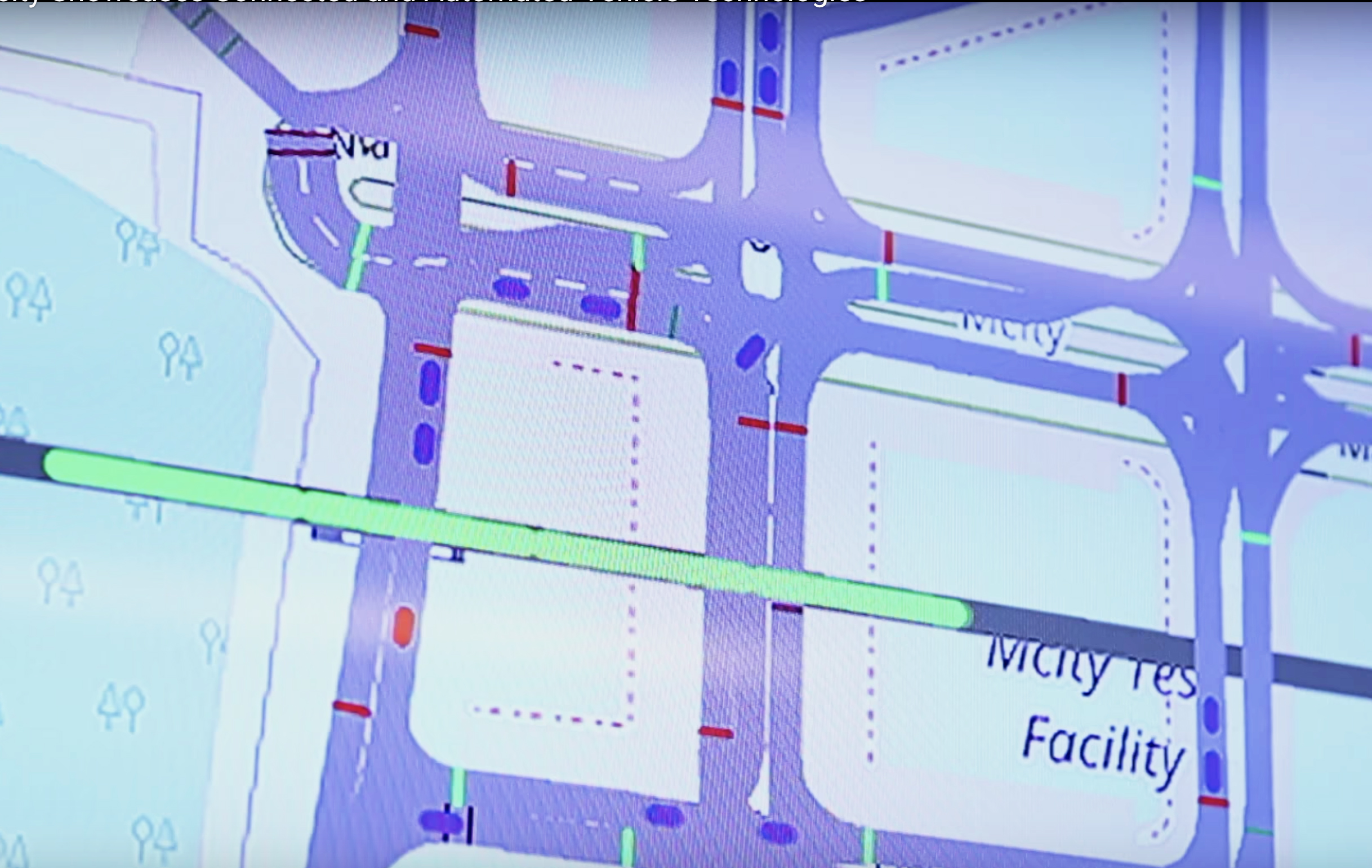 An image of the screen in the Michigan Traffic Lab while a virtual train (in green) travels through a rail crossing at Mcity. Real (red) and simulated vehicles (blue) react. Image credit: Screen capture from a video by Mike Wood