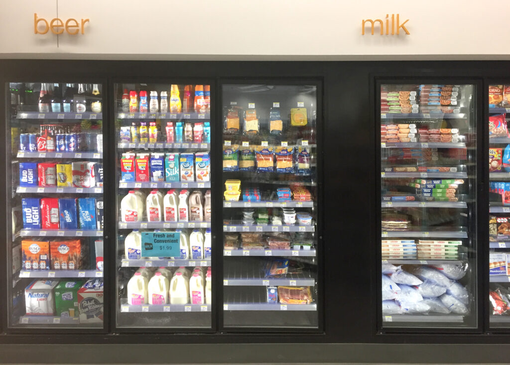 A convenience store refrigerator stocked with dairy products and alcoholic beverages. Image credit: Hans Anderson