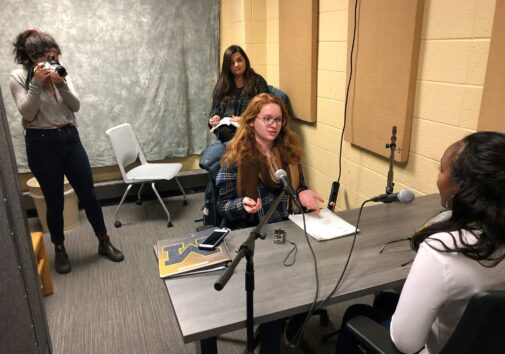 Hannah French interviews Asia Johnson while Zoey Horowitz shoots photos and Megan Diebboll takes notes.