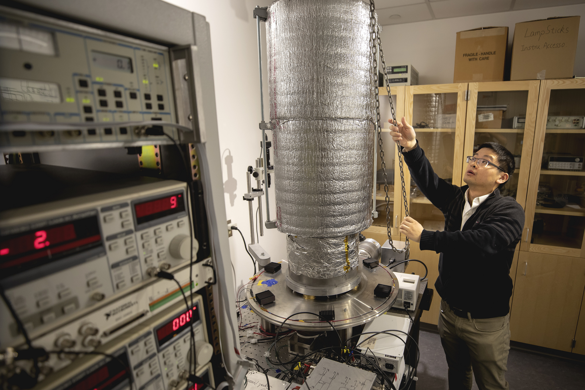 Linxiao Zhu shows the experimental platform that housed the calorimeter and photodiode. This system can damp vibrations from the room and building, steadily holding the two nanoscale objects 55 nanometers (0.000055 millimeters) apart. Image credit: Joseph Xu