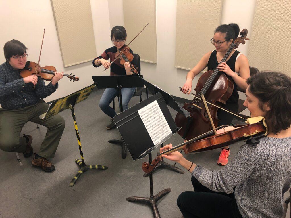 Estudantes do Quarteto de Cordas Ethos praticam para se apresentar em três prisões estaduais durante o intervalo de primavera.