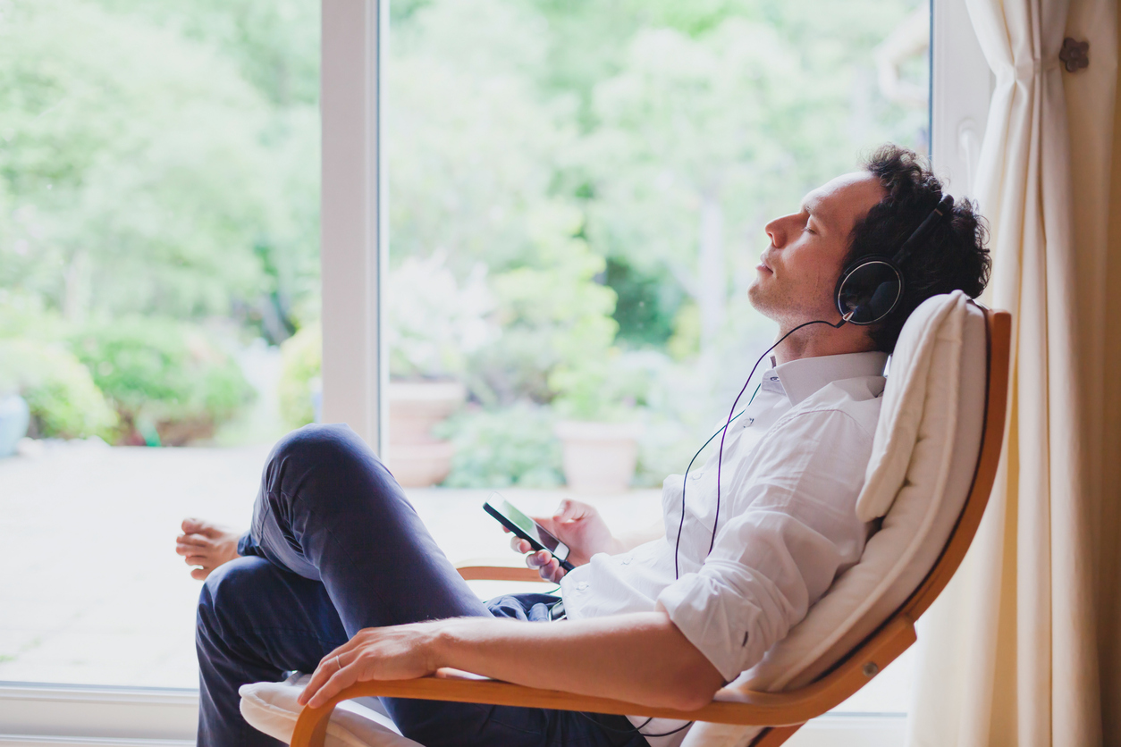Relaxed man in headphones sitting in deck chair. Image credit: iStock