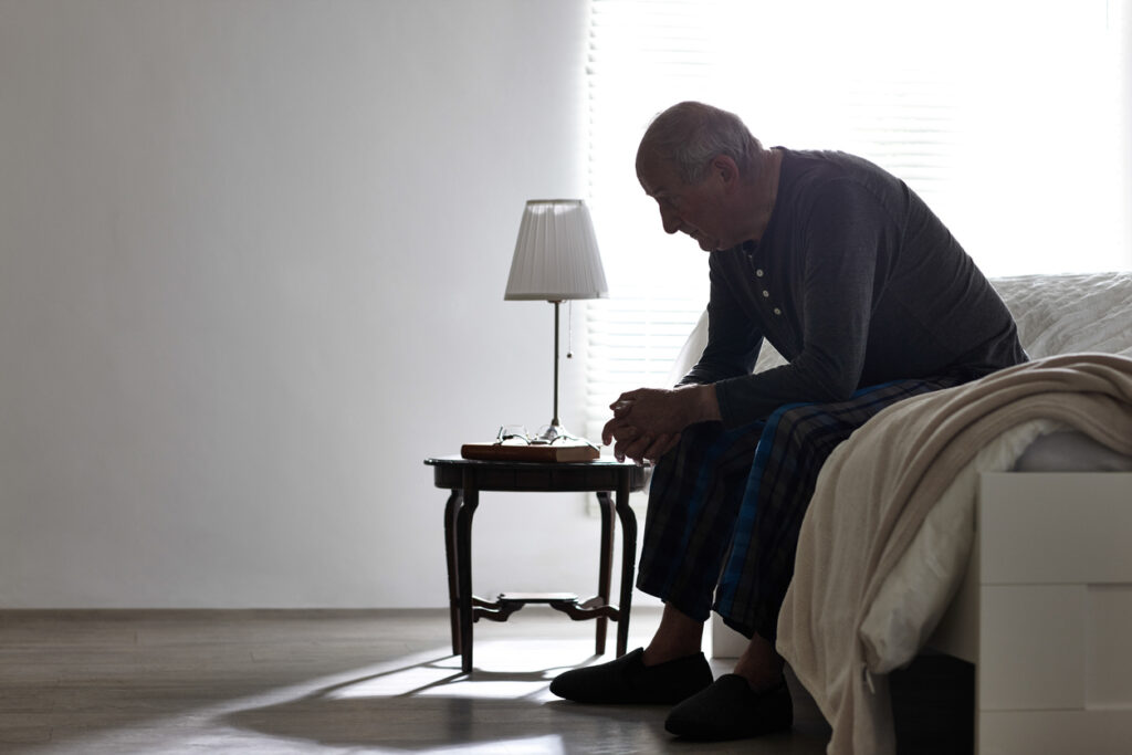 iStock image of an elderly man sitting on a bed.