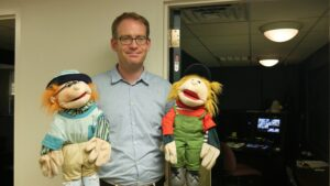 "Felix Warneken, associate professor of psychology, poses with puppets used in the ""trust experiment."" Image credit: Sean Moore, Michigan News"
