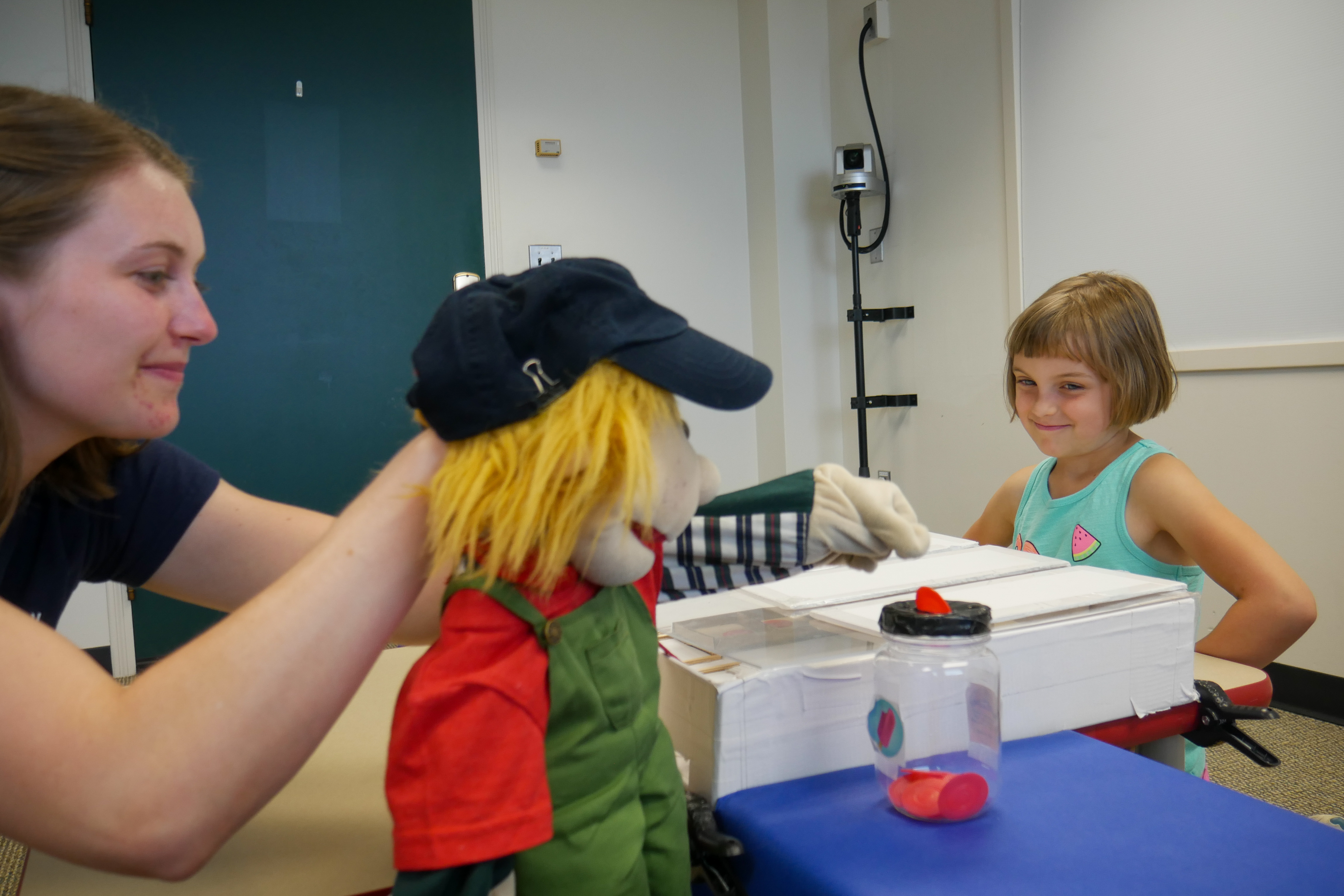 "The puppet places several coins in its ""bank"" rather than sharing half of them with the girl, much to her dismay. Image credit: Sean Moore, Michigan News"