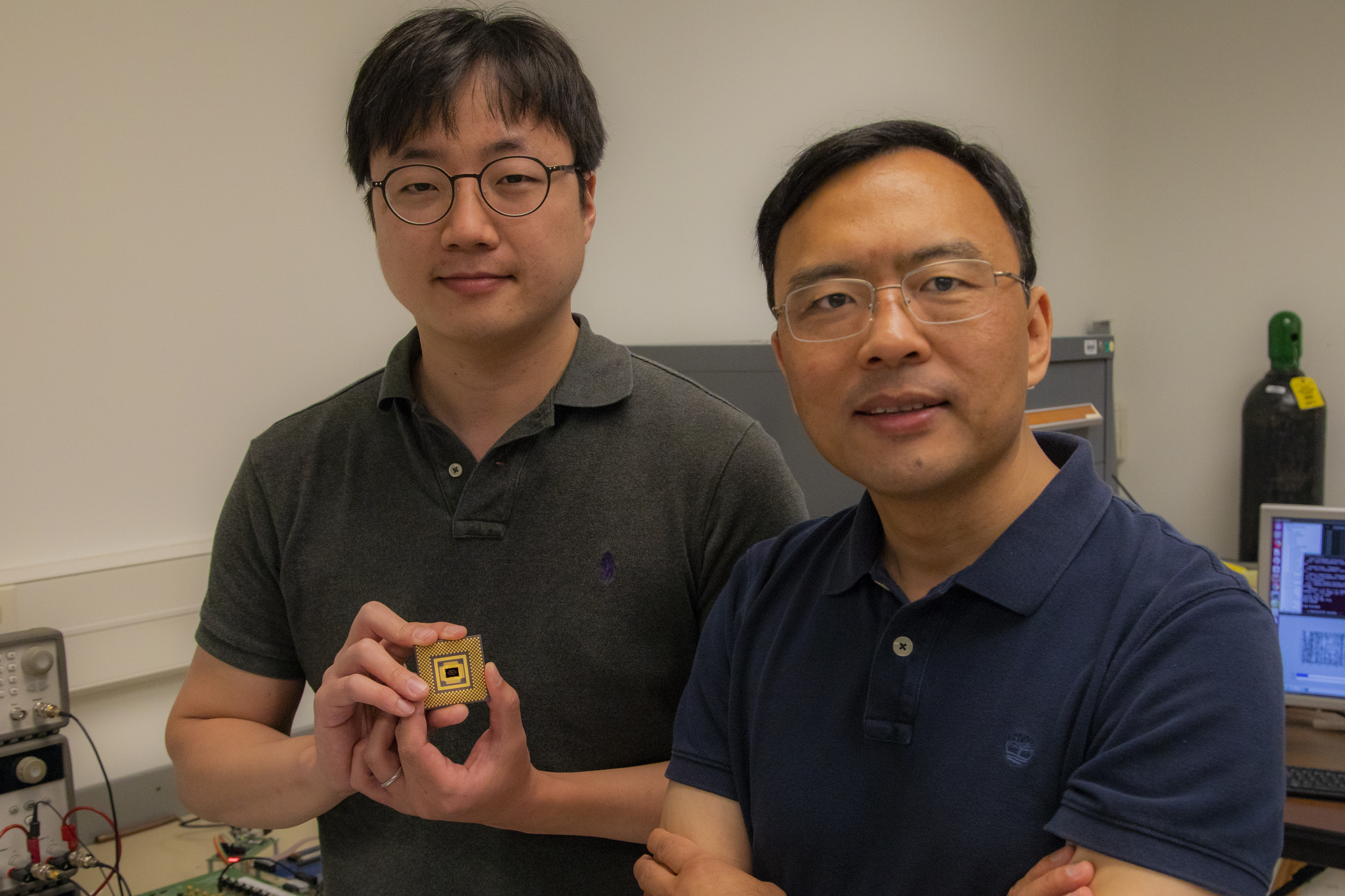 Wei Lu stands with first author Seung Hwan Lee, an electrical engineering PhD student, who holds the memristor array. Image credit: Robert Coelius, Michigan Engineering