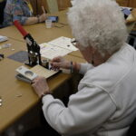 Juanita, age 87, prepping bicycle pattern buttons.