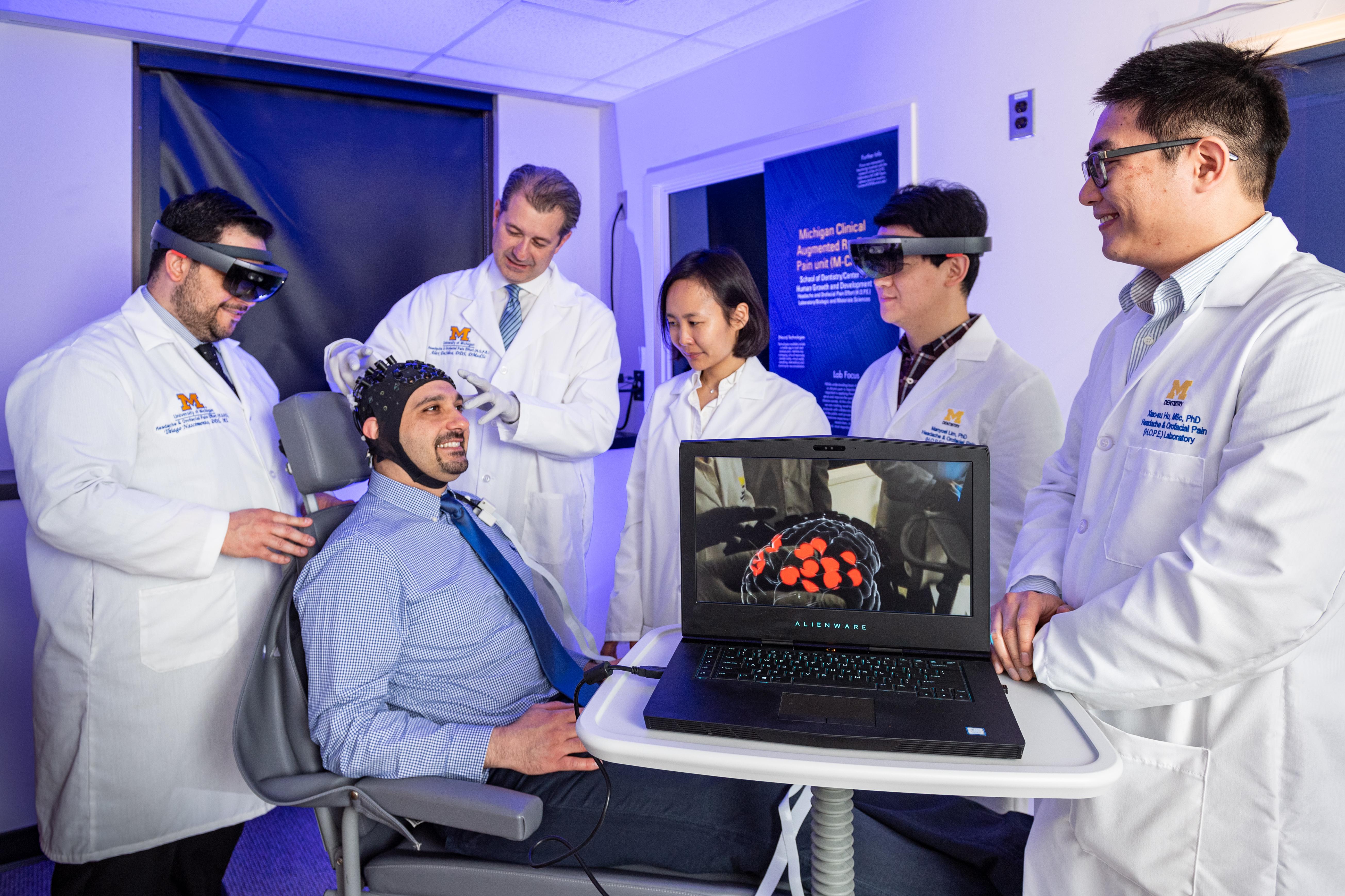 Hassan Jassar (sentado) usa o capacete com sensor, que detecta mudanças no fluxo sanguíneo e na oxigenação, sentindo a atividade cerebral. Essa informação é transmitida para um computador e interpretada. O pesquisador brasileiro, Thiago Nascimento, à esquerda, vê essa atividade cerebral em tempo real enquanto usa óculos de realidade aumentada, e a imagem do computador mostra essa assinatura específica de dor no cérebro. Da esquerda para a direita, também retratados, Dr. Alex DaSilva, Kim Dajung, Manyoel Lim, Xiao-su Hu.