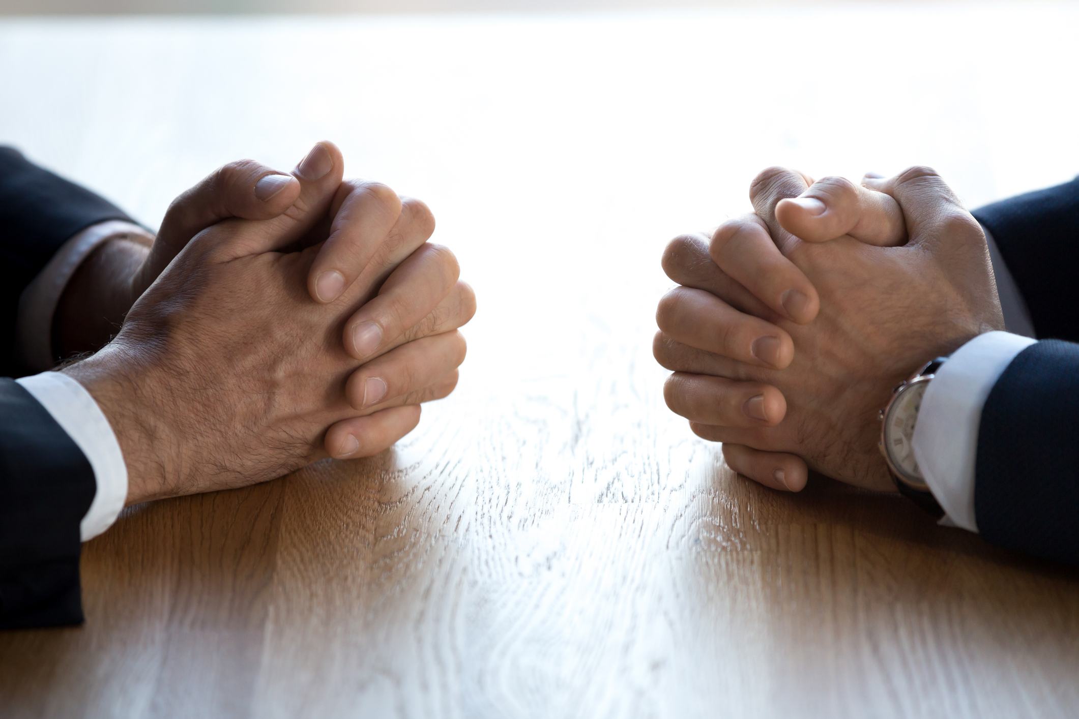 Clasped hands of two business men negotiators opponents opposite on table as politicians dialogue debate, applicant hr job interview, negotiating competitors, rivals confrontation challenge concept. iStock