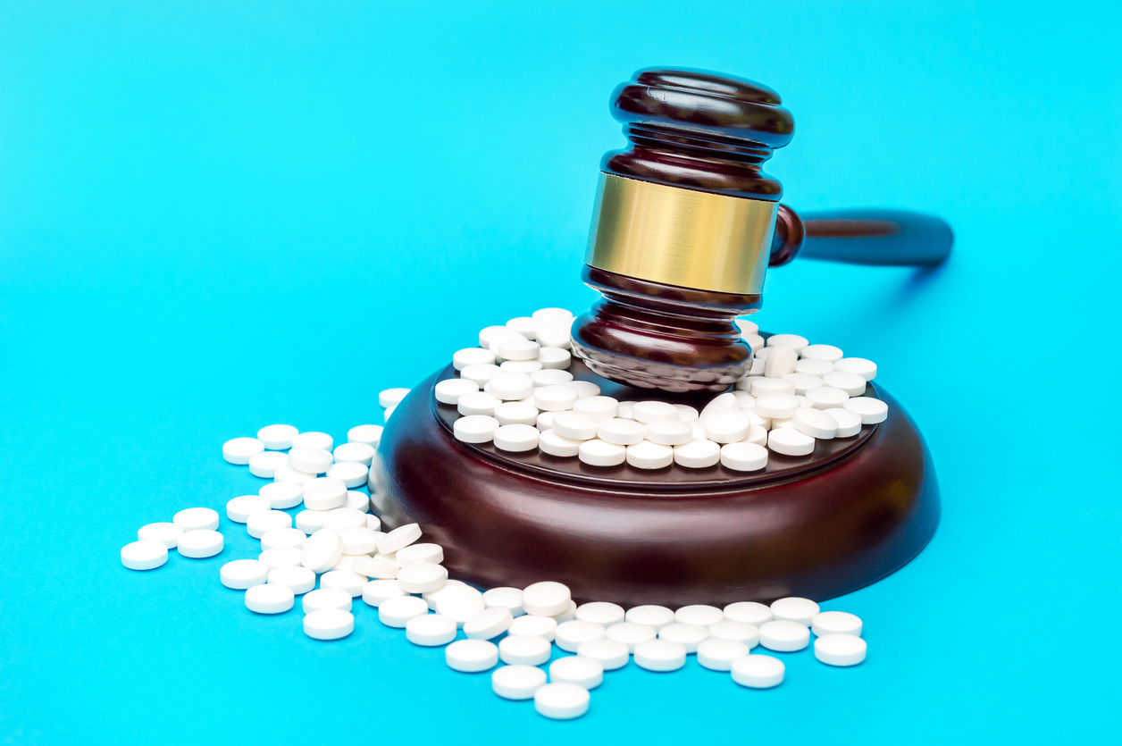Gavel with white pills on blue. Medical concept. Image credit: iStock