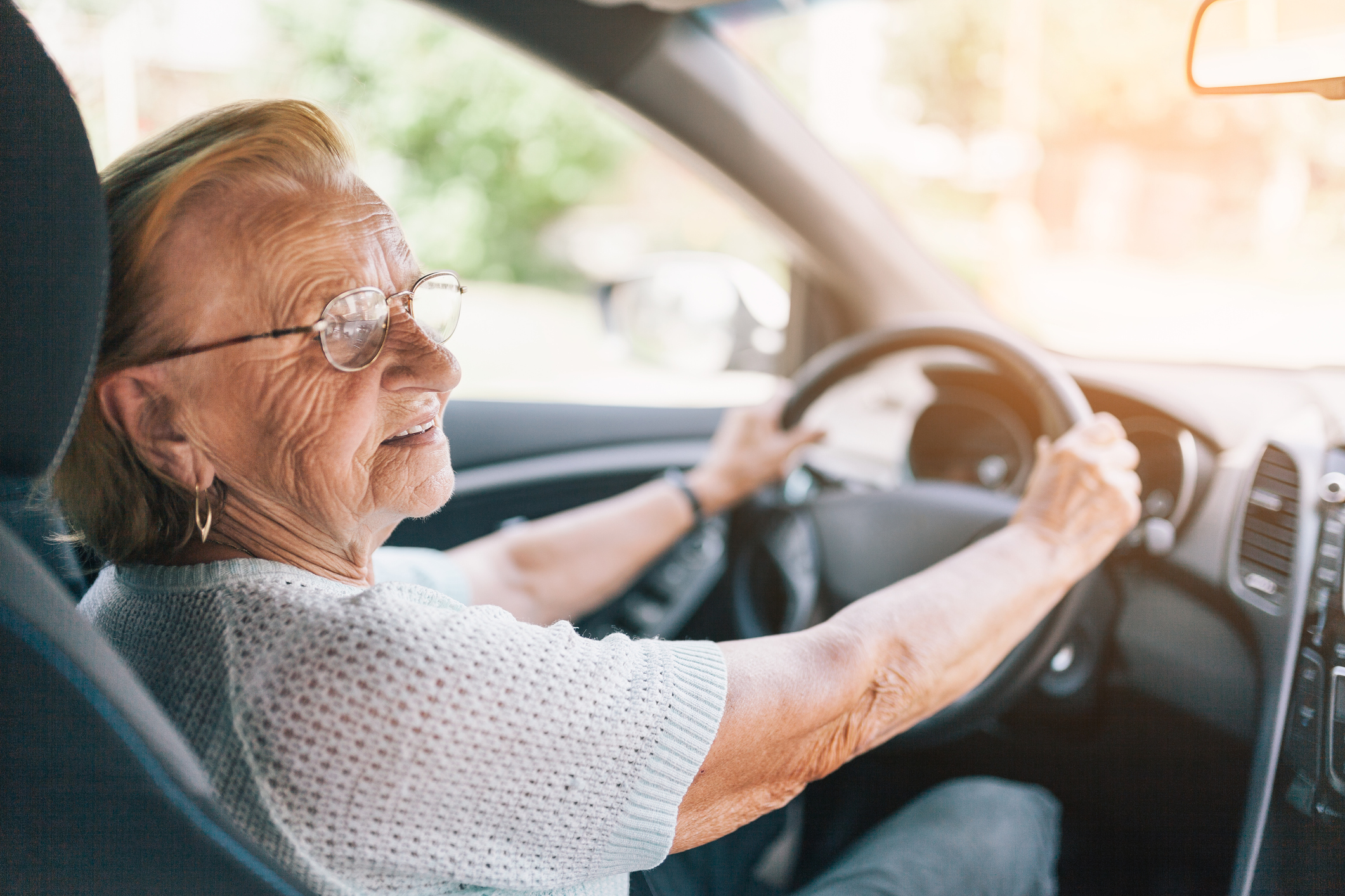 Elderly woman behind the steering wheel of a car. iStock.