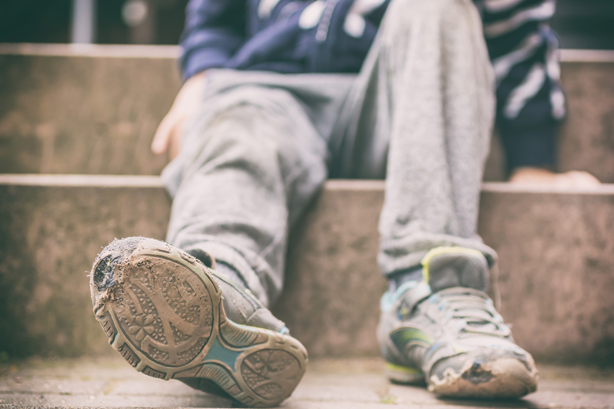 Child poverty symbolized by old broken shoes. Image credit: iStock