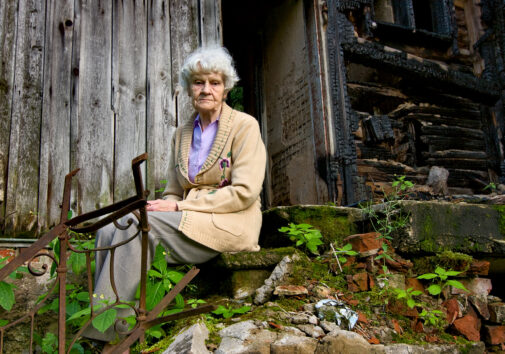 Elderly woman sitting outside a ruined building. Image credit: iStock
