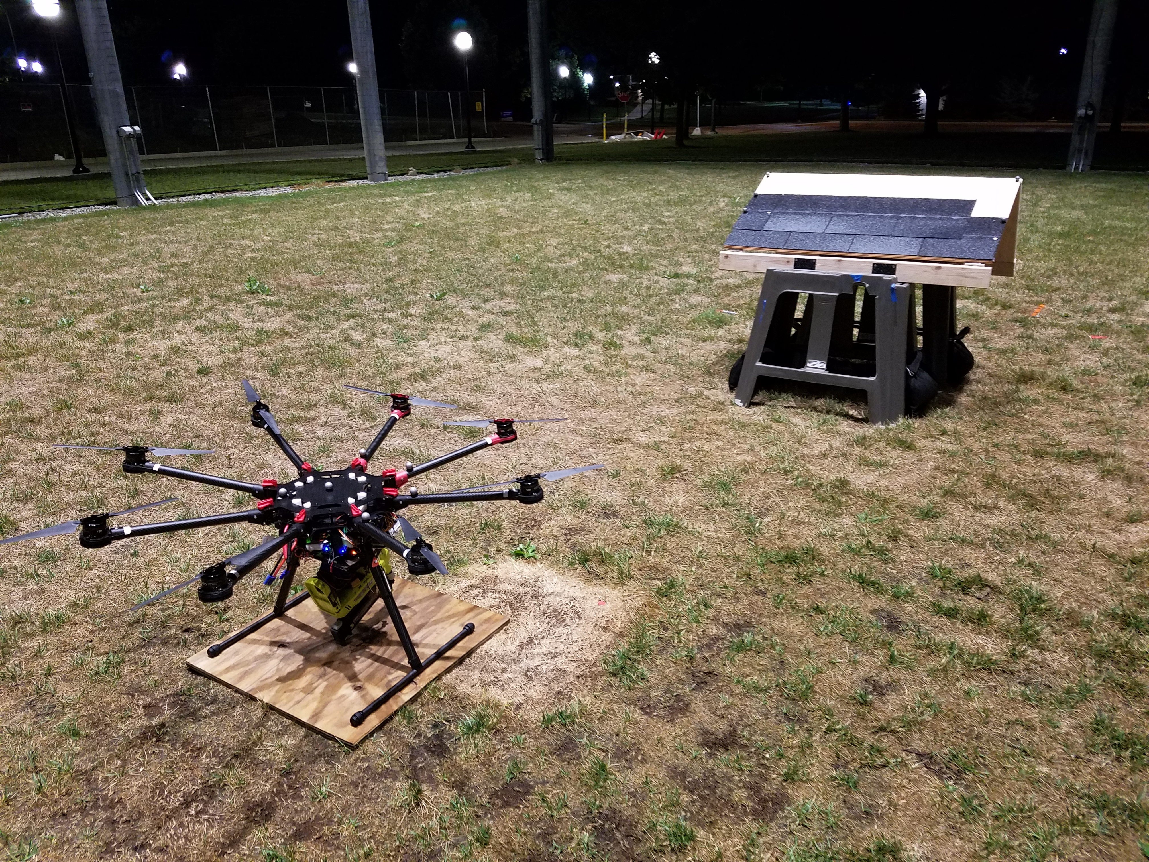 The roofing octocopter, equipped with a nail gun, is parked near the mock roof. By setting the wooden panel at different inclines, the researchers simulated roofs with different slopes. Image credit: Matthew Romano, Michigan Robotics