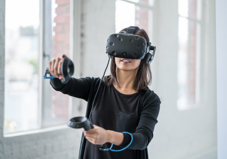An asian woman wearing a virtual reality headset.