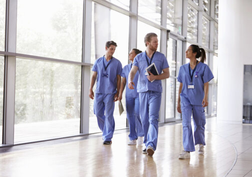 Four healthcare workers in scrubs walking. Image credit: iStock
