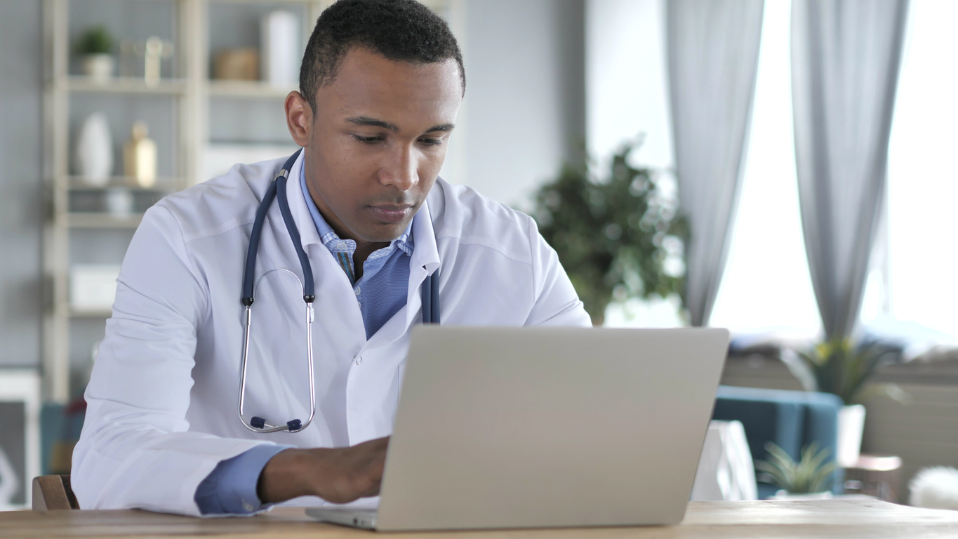 A doctor working on a laptop. Image credit: iStock